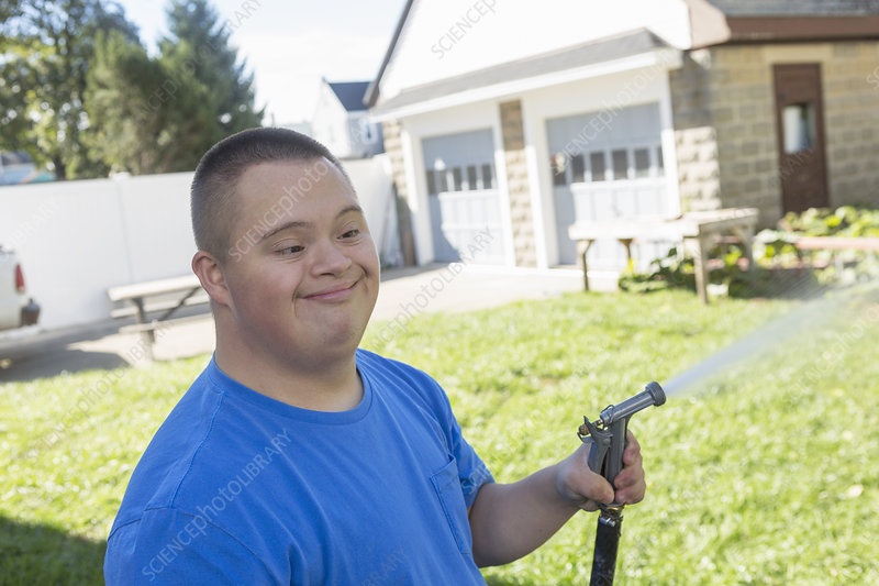 Teen with Down Syndrome watering garden