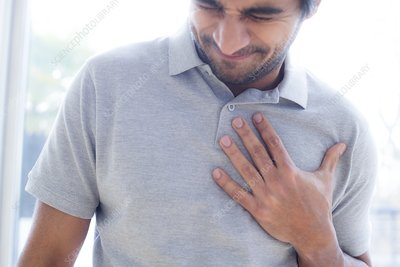 Man touching his chest in pain