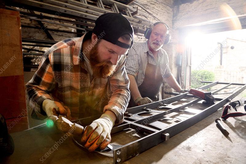 Senior blacksmith and son hammering metal