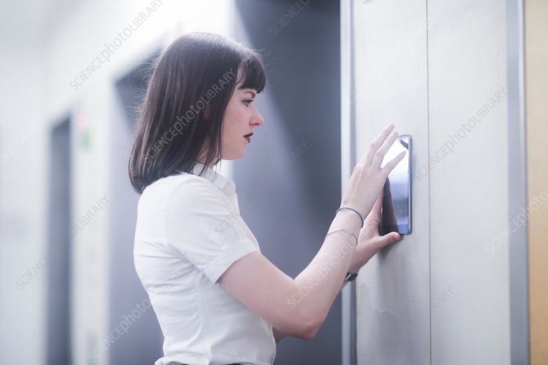 Woman using wall mounted touch screen control panel