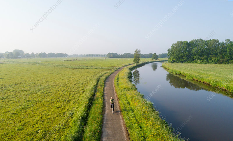 Boy cycling close to Mark river, Netherlands