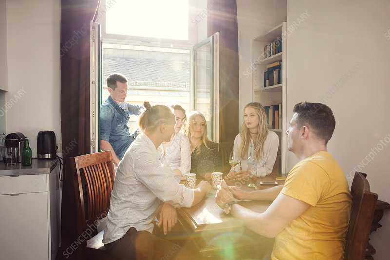 Group of friends chatting over drinks at home