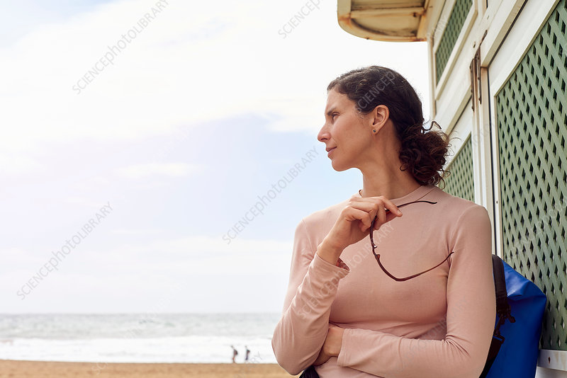 Female tourist looking over her shoulder at beach