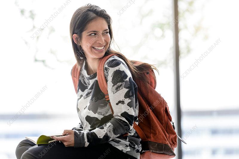 Female university student sitting on table