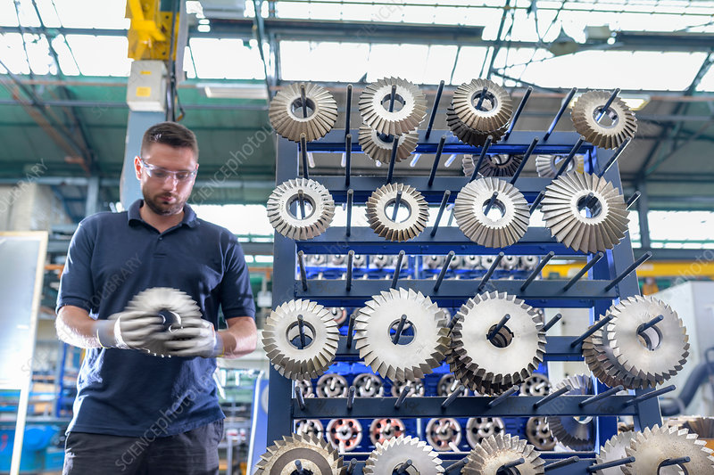 Engineer selecting cutting tool in gearbox factory
