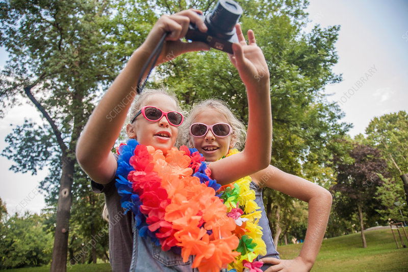 Girls in costume taking photograph with camera