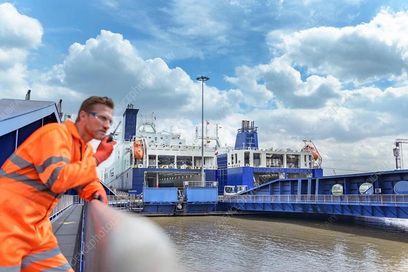 Ship's worker using walkie talkie on deck of ship in port
