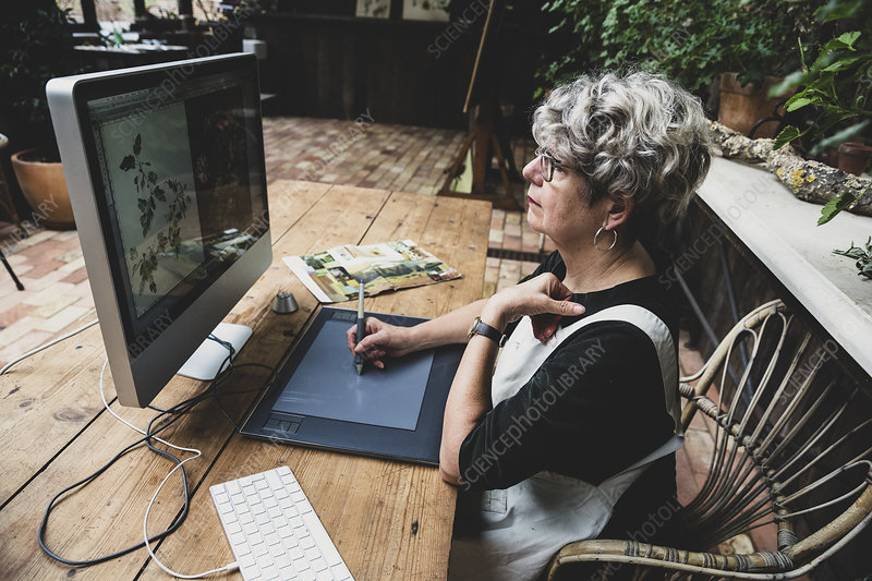 Senior woman wearing glasses working on desktop computer