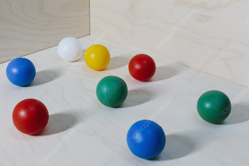 Multicoloured balls arranged on wood background, close up
