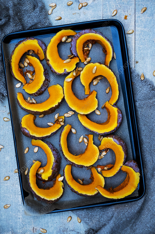 High angle close up of slices of pumpkin on a baking tray