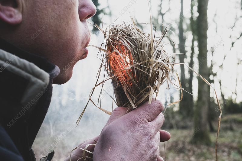 Close up of man blowing on bundle of straw, igniting fire