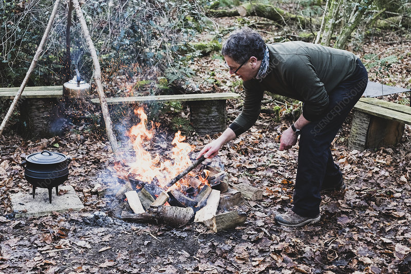 Man in forest stoking campfire, wooden tripod, iron pot