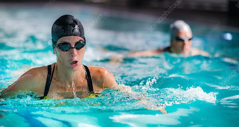 Woman swimming breaststroke in indoor pool