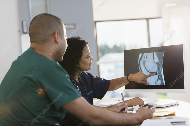 Nurses discussing digital x-ray at computer in clinic