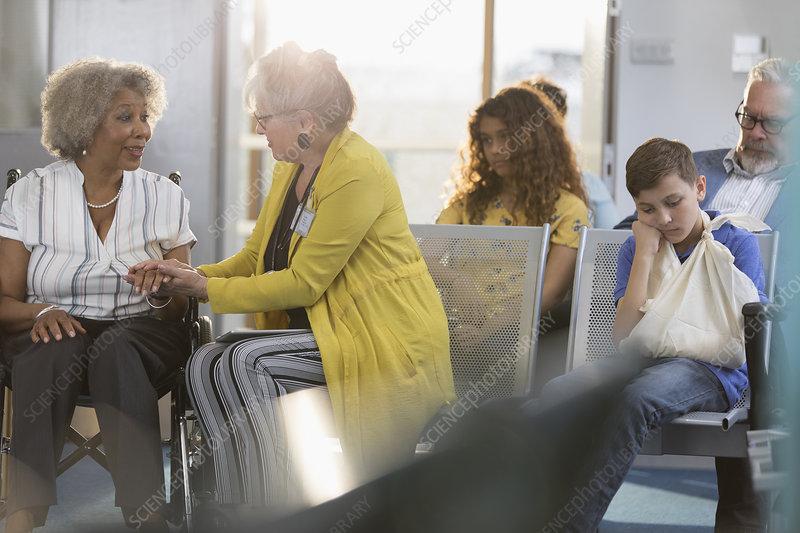 Doctor examining hand of patient in wheelchair