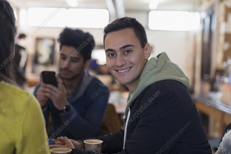 Portrait young man hanging out with friends in cafe