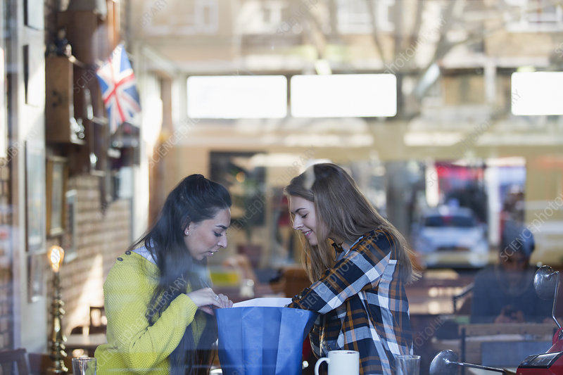 Young women looking into shopping bag in cafe window