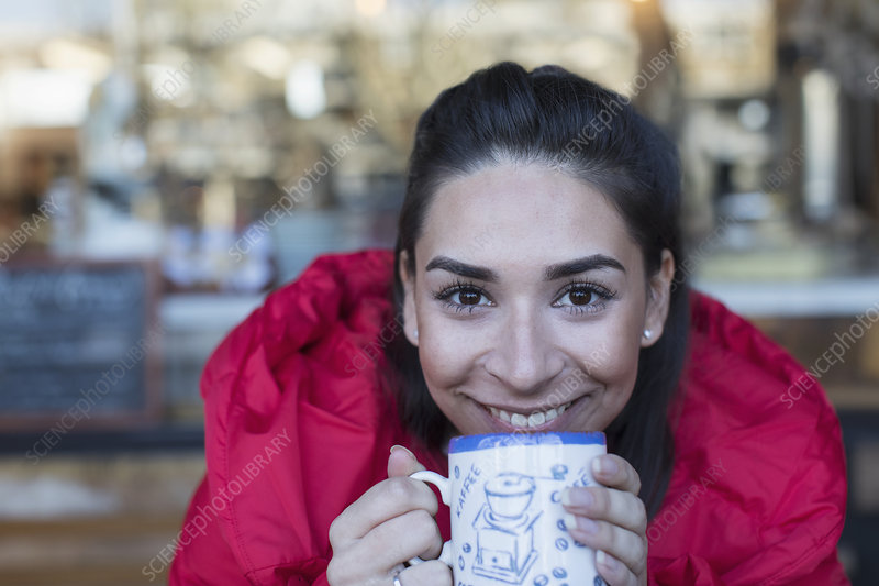Close up portrait happy young woman drinking coffee