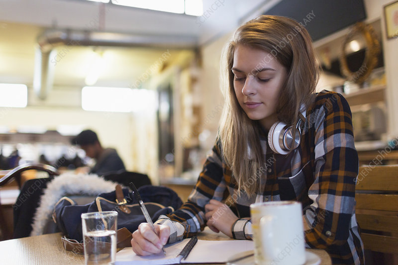 Young female college student studying in cafe