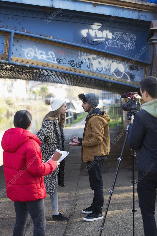 College film students filming under urban bridge