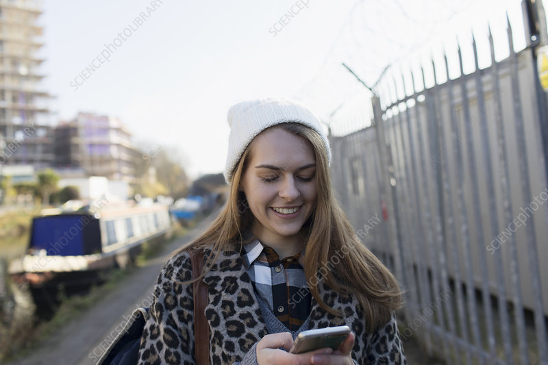 Young woman using smart phone along canal