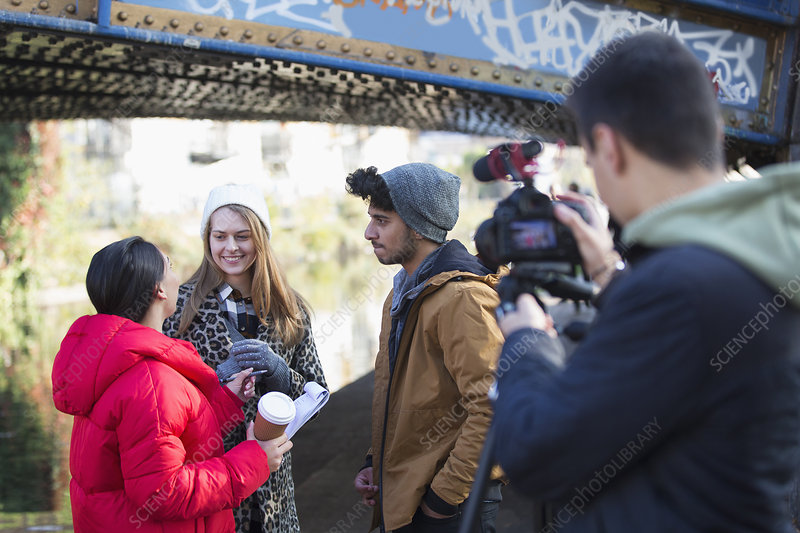 Young film students filming under urban bridge
