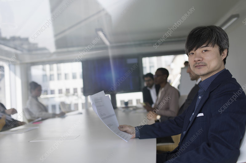 Businessman reviewing paperwork in conference room meeting
