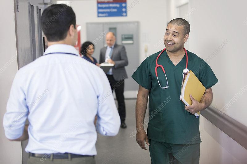 Surgeon greeting passing doctor in hospital corridor