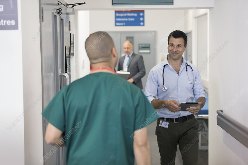 Male doctors greeting, passing each other