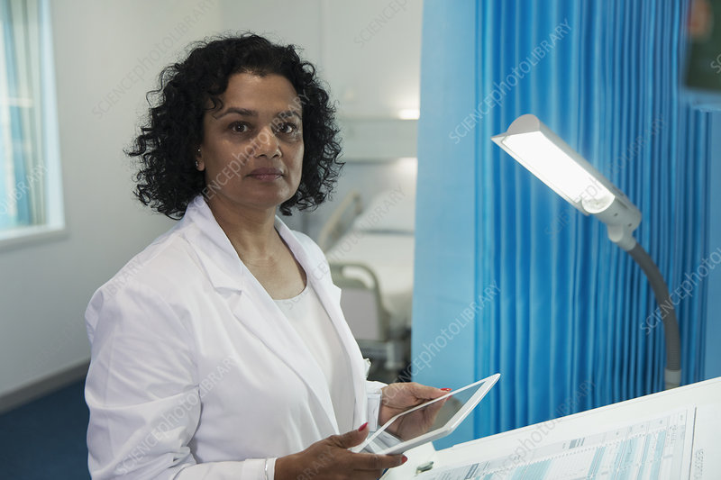 Confident, determined doctor using tablet in hospital room