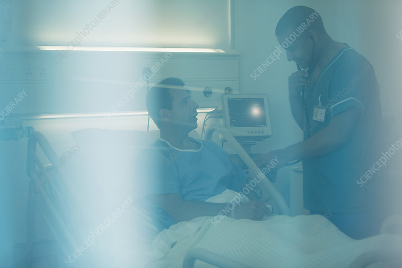 Male nurse examining patient in hospital bed