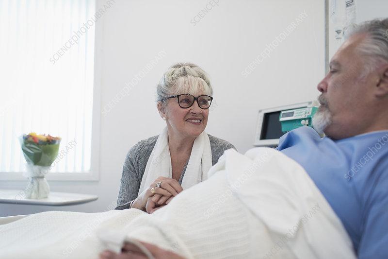 Senior woman visiting, comforting husband resting