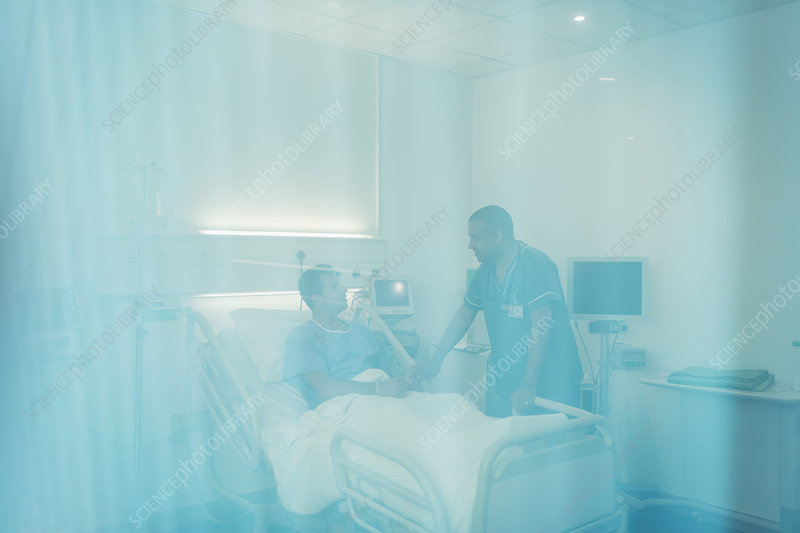 Male nurse talking with patient in hospital room