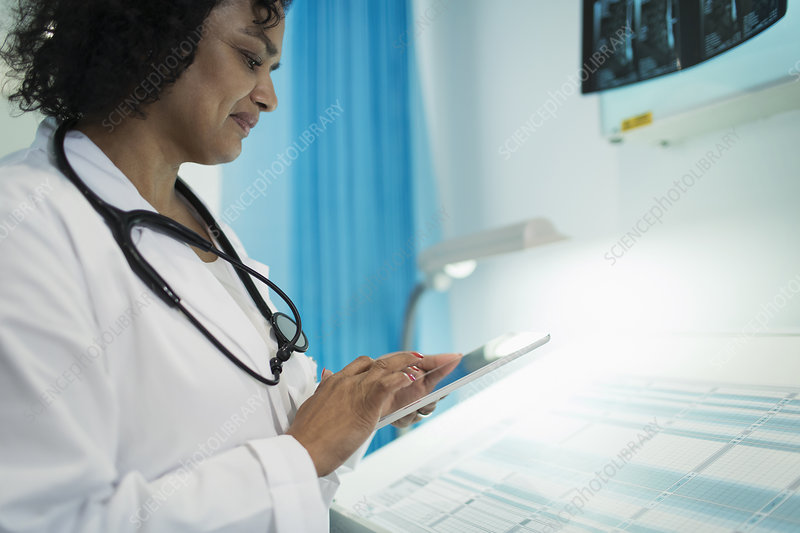 Female doctor using digital tablet in hospital room