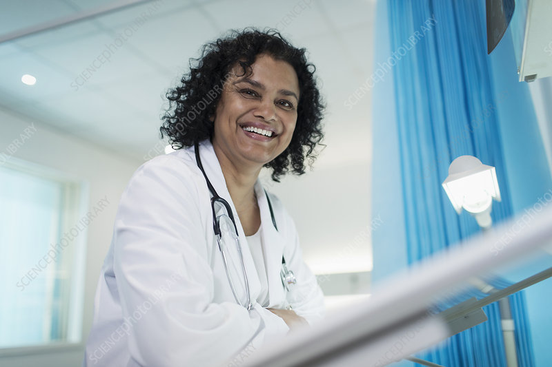 Portrait confident, female doctor in hospital room