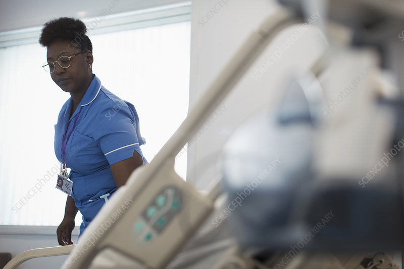 Female nurse making hospital bed