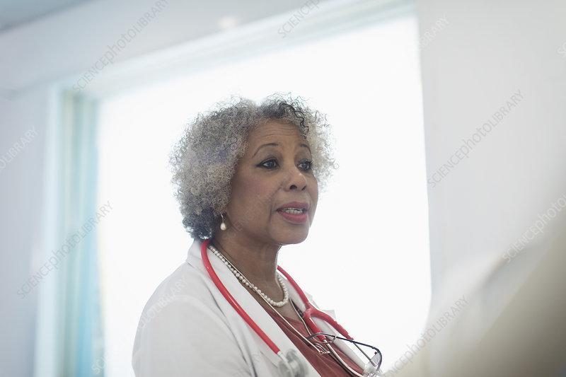 Senior female doctor making rounds, talking in hospital