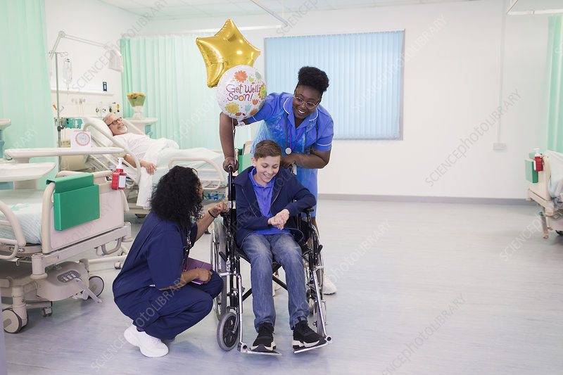 Doctor and nurse pushing boy patient in wheelchair