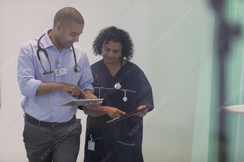 Doctors with digital tablets talking in hospital