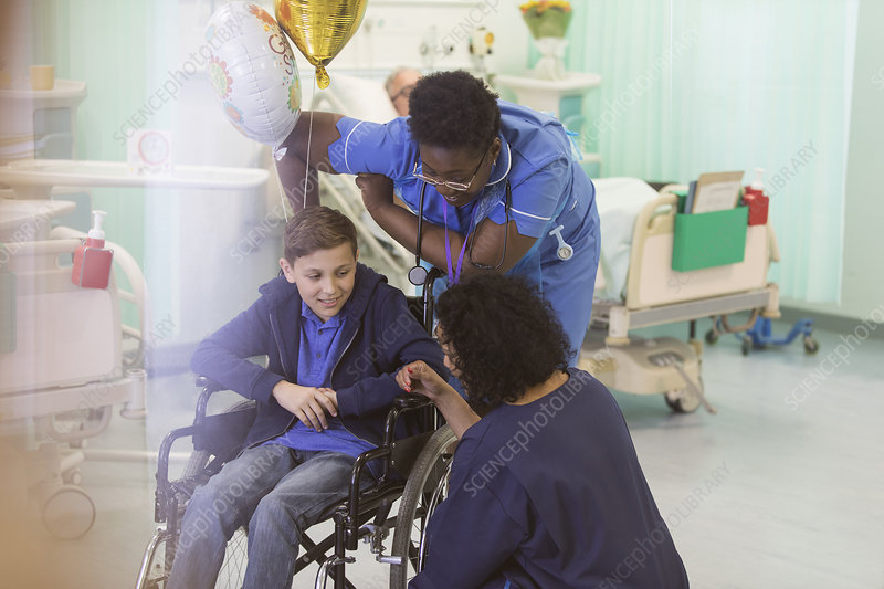 Doctor and nurse talking with boy patient in wheelchair