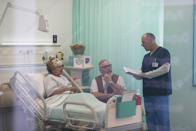Doctor with medical chart talking with couple