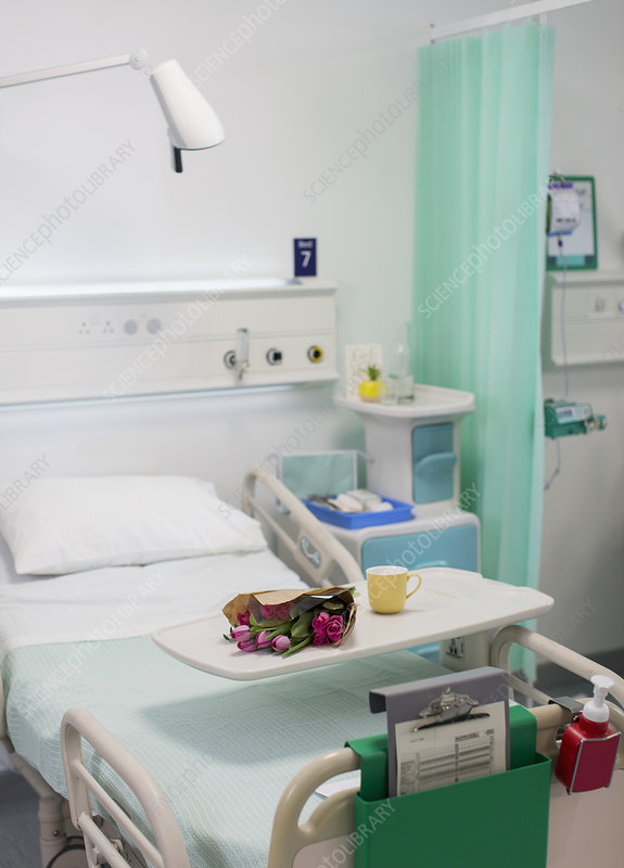 Flowers on tray over hospital bed in vacant hospital room