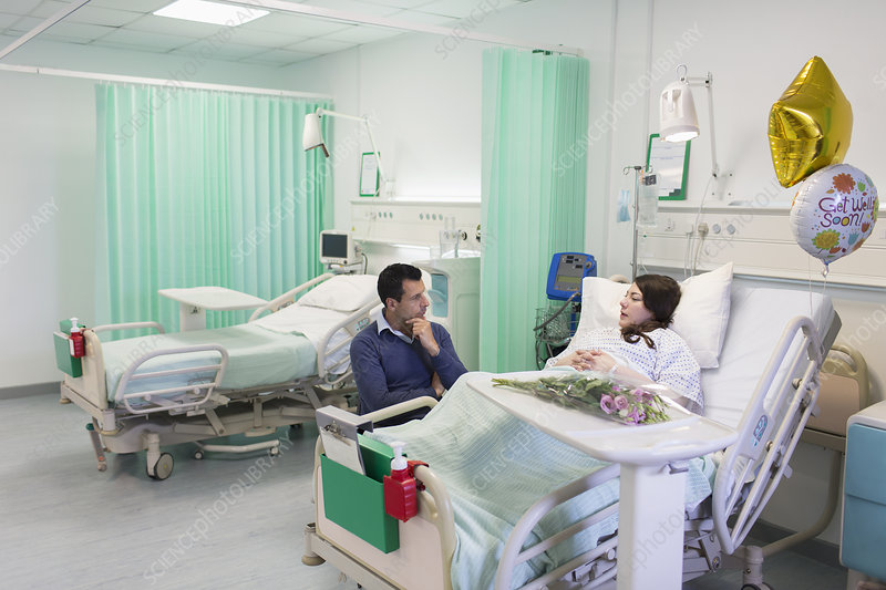 Man visiting, talking with wife resting in hospital ward