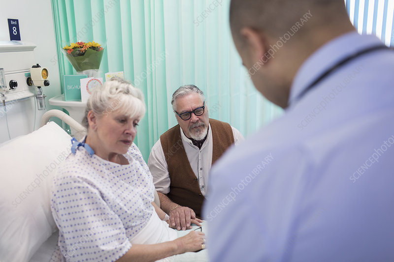Doctor making rounds, talking with couple in hospital room