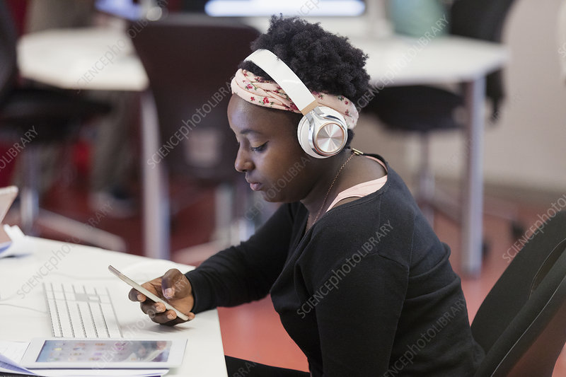 Female student with headphones using smart phone