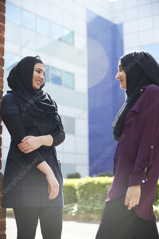 Women friends in hijabs talking outside sunny building