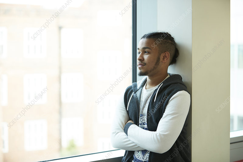 Thoughtful teenage boy looking out window