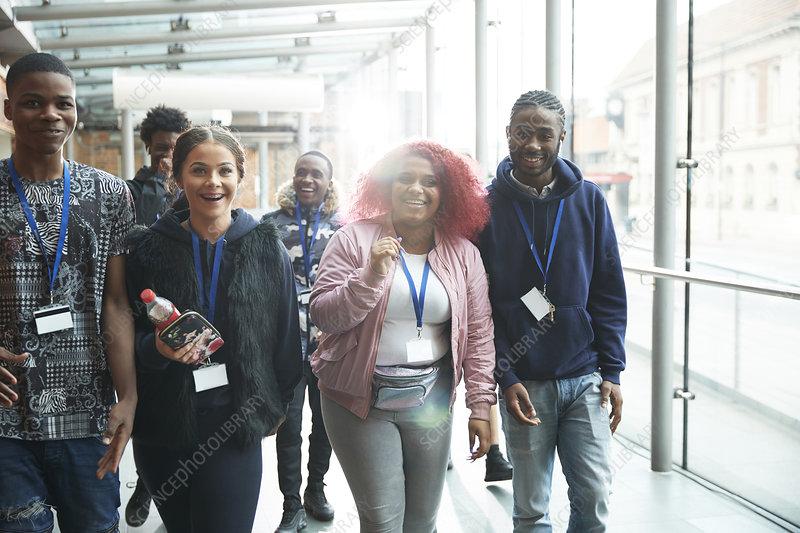 Happy high school student friends walking in corridor