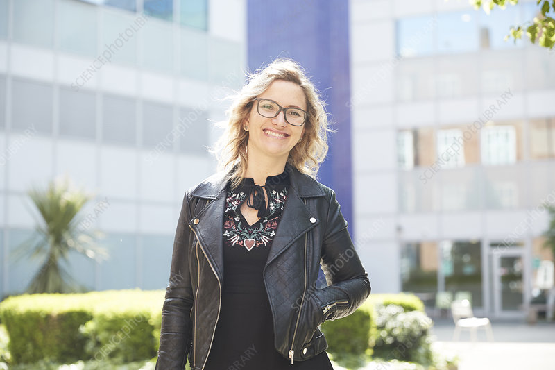 Portrait woman in leather jacket outside sunny building