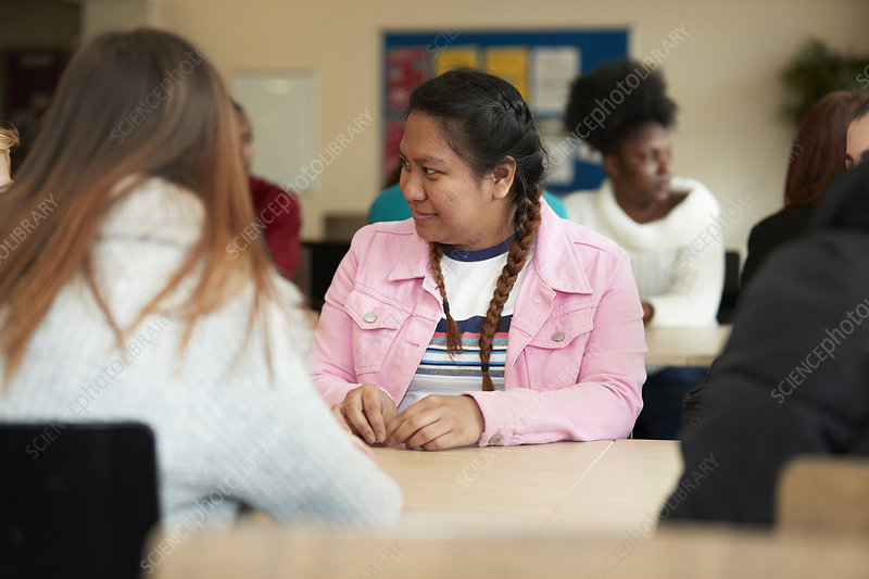 Young college student listening to classmate in classroom